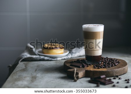 Cup of coffee with coffee beans, donut and chocolate on the table. Horizontal - stock photo