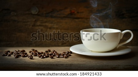 Cup of coffee with coffee beans on a wooden - stock photo