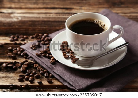 Cup of coffee with coffee beans on brown wooden background - stock photo