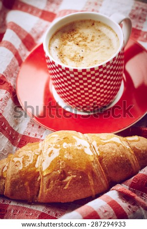 Cup of coffee with croissant on fabric background - stock photo