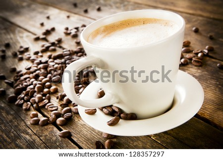 Cup of coffee with foam, wood table. - stock photo