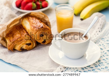 Cup of coffee with french croissant with chocolate served with fruit. Selective focus - stock photo