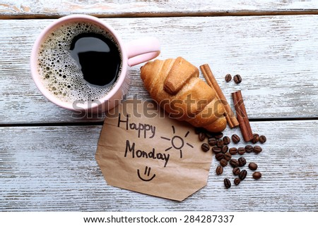 Cup of coffee with fresh croissant and Happy Monday massage on wooden table, top view - stock photo