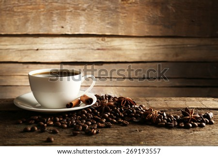 Cup of coffee with grains and spices on wooden background - stock photo