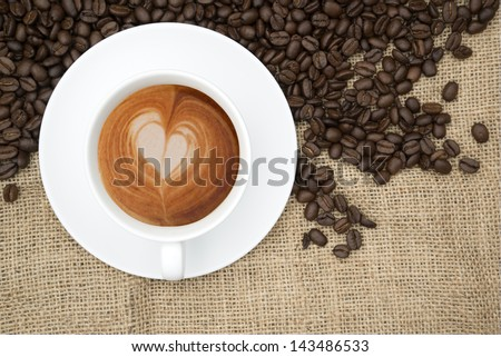 Cup of coffee with heart shape in foam and beans on hessian background - stock photo