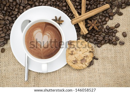 Cup of coffee with heart shape in foam with coffee beans and cinnamon sticks and star anise and cookie on hessian background - stock photo