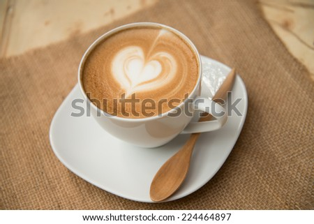 Cup of coffee with heart shape on hessian background - stock photo