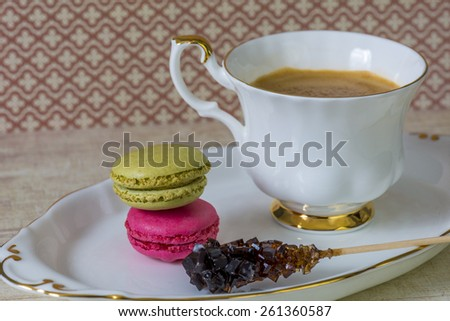 cup of coffee, with macarons, and crystallized sugar sticks. on a vintage background - stock photo