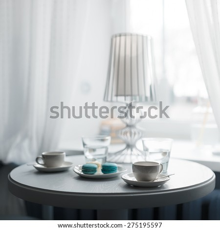 Cup of coffee with macaroon on the table in a coffee shop - stock photo