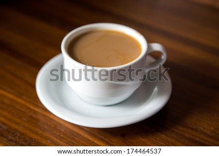 Cup of coffee with milk on a wooden table - stock photo