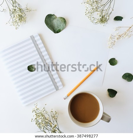Cup of coffee with milk, sketchbook, pencil, green leaves and dried flowers. Overhead view. Isolated on white. Flat lay, top view - stock photo