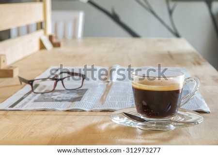 Cup of coffee with newspaper and glasses on table - stock photo