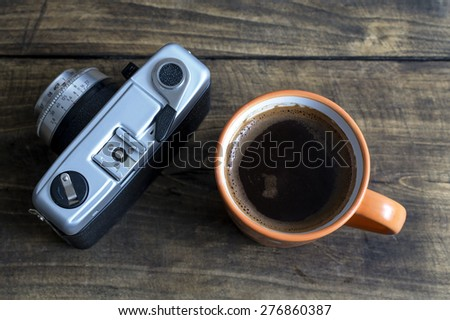 Cup of coffee with retro camera, from above - stock photo