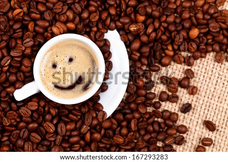 Cup of coffee with smiley face on coffee beans and burlap background  - stock photo
