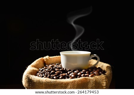 Cup of coffee with smoke and coffee beans in burlap sack, This photo is available without smoke - stock photo