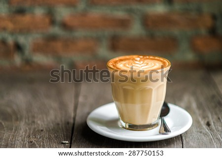 Cup of coffee with tree leaves pattern in reveal cup on wooden background, Close up cup of coffe red brick background - stock photo
