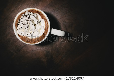 Cup of coffee with whipped cream on a brown table. - stock photo