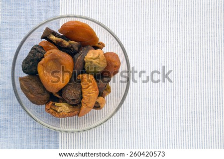 Cup of dried fruits on the blue and white weave cloth background - stock photo