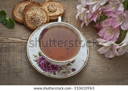 Cup of english tea, homemade bakery, puff cookies with sesame seeds on plate and beautiful flowers - stock photo