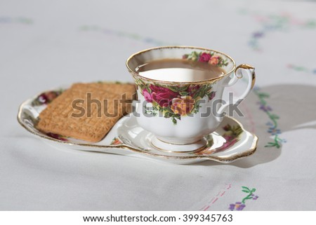 Cup of English tea on a table cloth with biscuits - stock photo