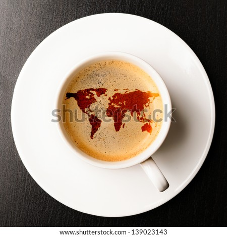cup of fresh espresso on table, view from above. Earth silhouette is from visibleearth.nasa.gov - stock photo