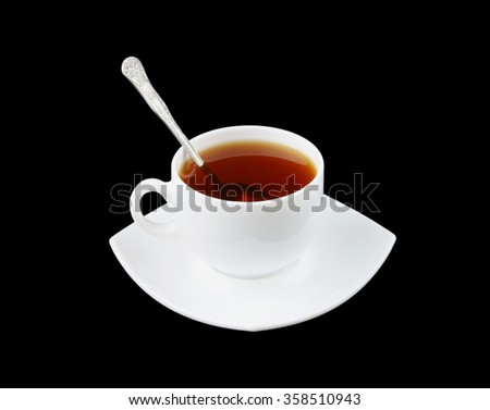 Cup of fresh tea with spoon and saucer isolated on black - stock photo
