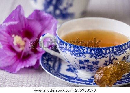 Cup of freshly brewed black tea served in a dainty blue and white porcelain cup and saucer with a sugar crystal stick for sweetening - stock photo