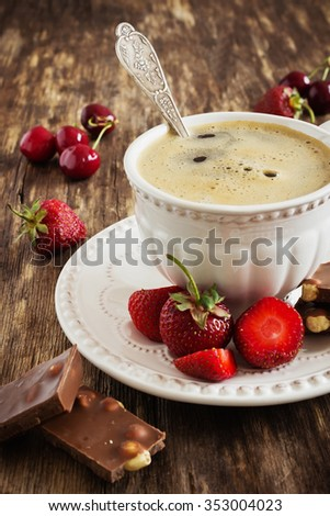 cup of freshly brewed coffee, chocolate and fruit on the old wooden background. rustic style. selective focus - stock photo