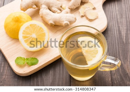 Cup of ginger tea with lemon on wooden background. - stock photo