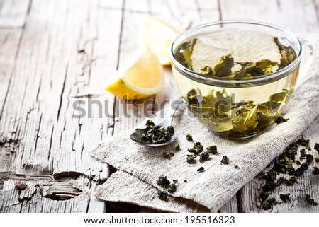cup of green tea and lemon on rustic wooden table  - stock photo