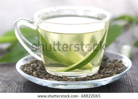 Cup of green tea on a wooden table - stock photo