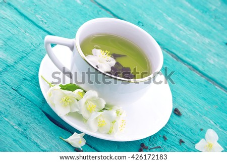 Cup of green tea with jasmine flowers on turquoise rustic wooden background. - stock photo