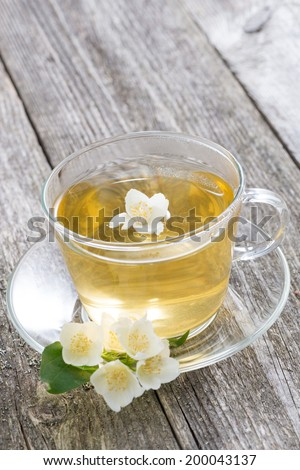 cup of green tea with jasmine on wooden background, top view - stock photo