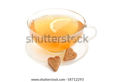 Cup of green tea with lemon and heart-shaped cane sugar on white background - stock photo