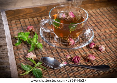 Cup of green tea with mint and dried rose buds on old wooden tray - stock photo
