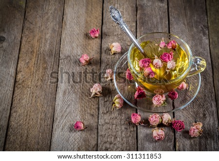 Cup of green tea with teaspoon and dried rose buds on old wooden table, empty space for text - stock photo