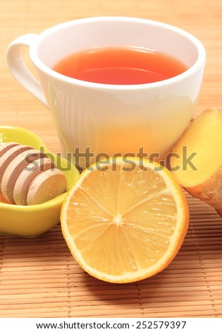 Cup of healthy tea with honey ginger and lemon on wooden background, concept for healthy nutrition - stock photo