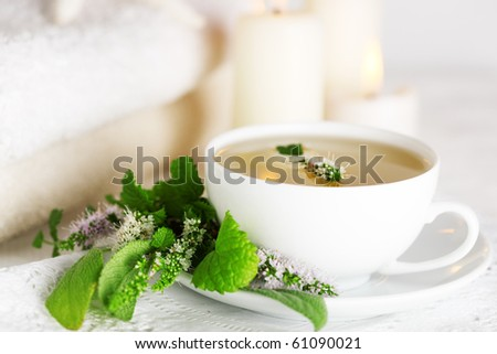 cup of herbal tea and edible flowers - stock photo