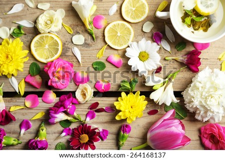 Cup of herbal tea with beautiful flowers, on wooden background - stock photo
