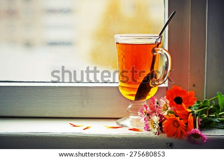 cup of herbal tea with flowers on wooden background  - stock photo