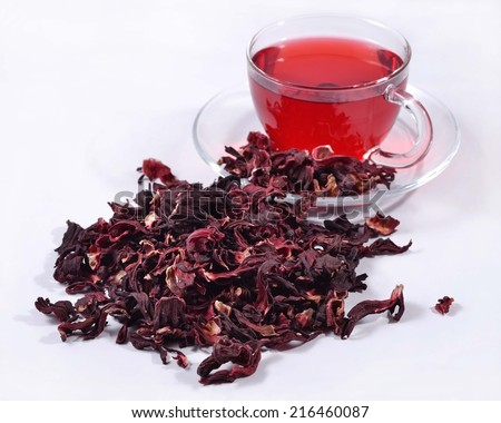 Cup of hibiscus tea and a heap of dried petals of hibiscus  - stock photo