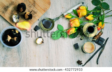 Cup of hot black coffee with vanilla sticks and chocolate and flowers on vintage wooden background, selective focus ,view from above, rustic life style - stock photo