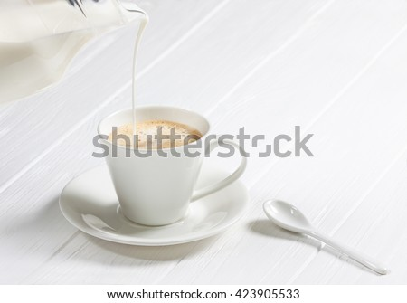 cup of hot cappuccino coffee on a white wood table. Milk being poured into a cup of coffee. Adding milk. - stock photo