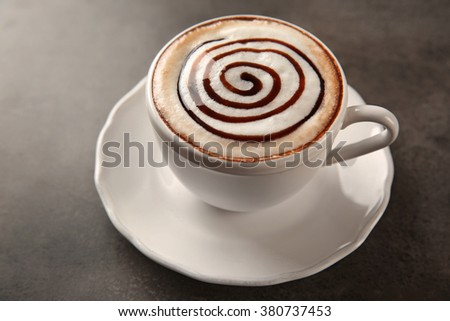 Cup of hot cappuccino with chocolate syrup on grey table - stock photo