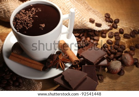cup of hot chocolate, cinnamon sticks, nuts and chocolate on wooden table - stock photo
