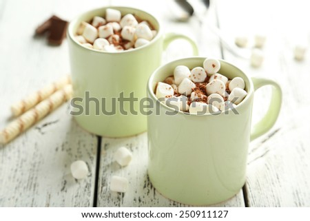 Cup of hot chocolate with marshmallows on white wooden background - stock photo