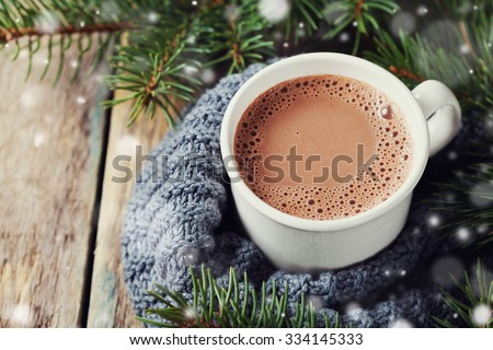 Cup of hot cocoa or hot chocolate on knitted background with fir tree and snow effect, traditional beverage for winter time - stock photo