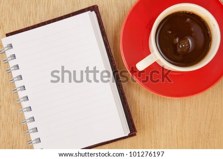 cup of hot coffee and book on wood background - stock photo