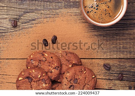 Cup of hot coffee and chocolate cookies with nuts on old wooden table. Top view - stock photo