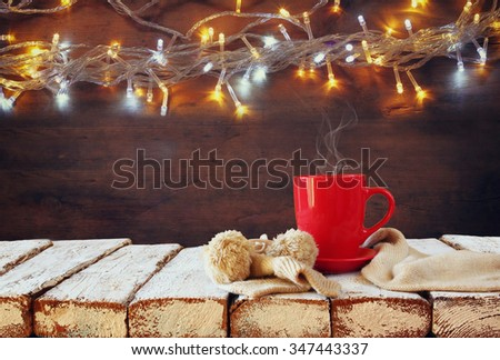 Cup of hot coffee and cozy knitted scarf on wooden table in front of garland lights background  - stock photo